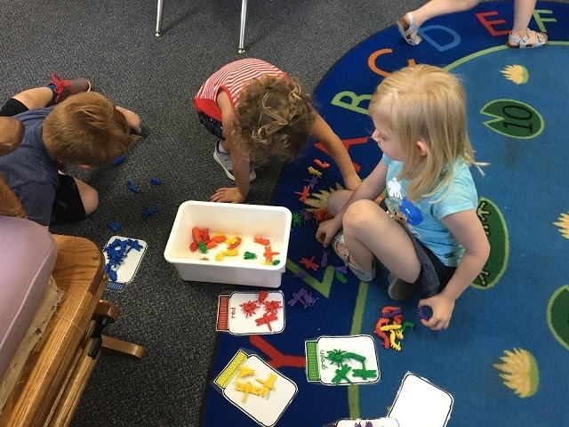Preschool friends help each other sort by color
